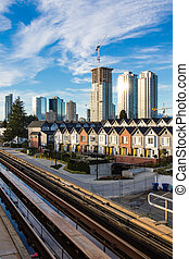Brand new townhouses in a row on bright sunny day with Highrises in the background.