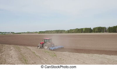 Brand new tractor on field working. Tractor plowing land....