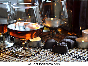 Brandy and chocolate - A glass of brandy, chocolate sweets...
