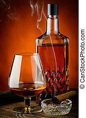 Brandy and cigar - still life with glass and bottle of...