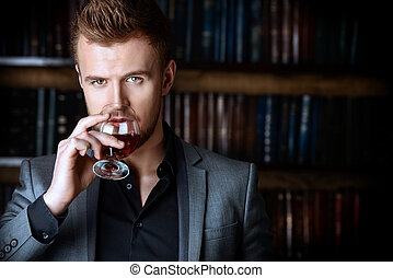 brandy - Elegant man in a suit with glass of beverage stands...