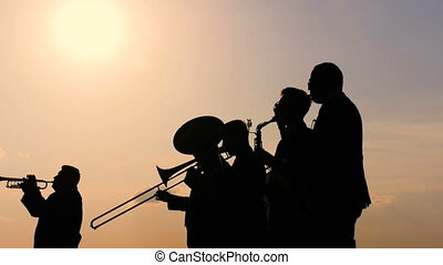 Unrecognizable brass band silhouette playing wind instruments at city street holiday, festival or carnival. Entertainment, music, urban culture and art concept