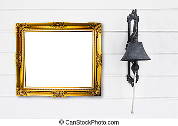 Brass bell with vintage frame on white wood wall.