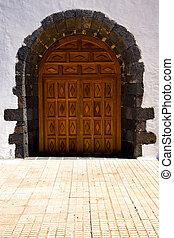 brass brown knocker in a brown closed wood  church door