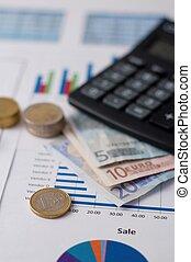 Brass coin on sheet of paper near a calculator