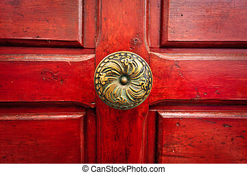 Brass doorknob and red door