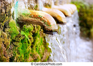 brass fountain water source spring with green moss
