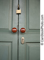 Brass Padlock on Wooden Green Gate with brown round handel
