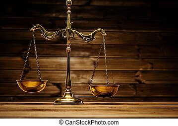 Brass scales over wooden background