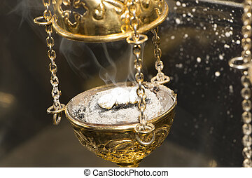 Brass thurible liturgy censer with burning incense in it -...