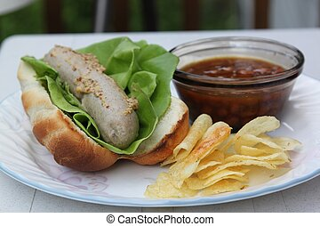 Bratwurst baked beans and chips - A plate of summer fare;...