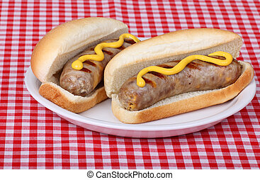 Two bratwursts on buns with mustard on a plate