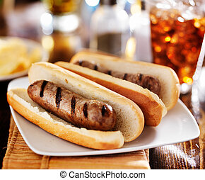 bratwursts that were grilled with cola and potato chips in...