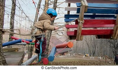 Brave toddler boy in protective helmet with safety belt goes up log stairs spending time at high rope course on autumn day