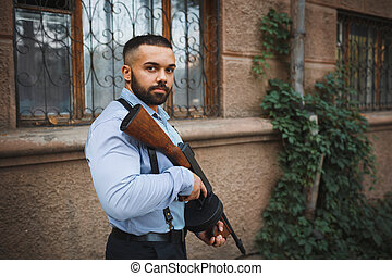 Brave cool man holding a gun on an urban background. A handsome gangster in a blue shirt. Copy space.