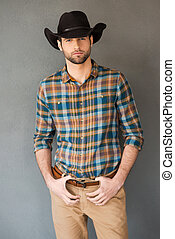 Brave cowboy. Handsome young man wearing cowboy hat and looking at camera while standing against grey background