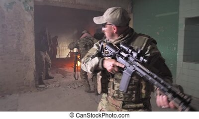 Military men helping injured comrade to leave battlefield, two military men carrying wounded soldier, others covering retreat with weapons. Squad of warriors in abandoned building insuring evacuation