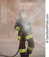 firefighter in action with the foaming agent during an emergency