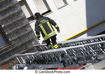 firefighter walking on extended ladder of firetrucks during the fire