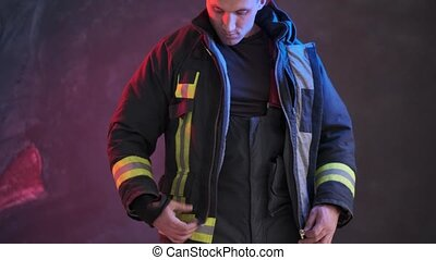 Firefighter wears uniform while standing against a gray wall