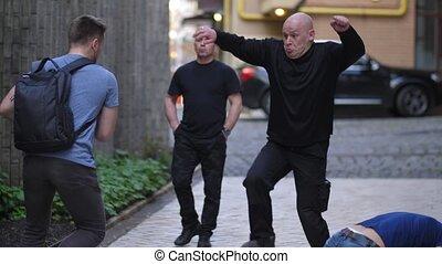 Close-up of armed criminals attacking male walking in city street. Fearless man knocking three muggers applying Krav Maga self defence and running away
