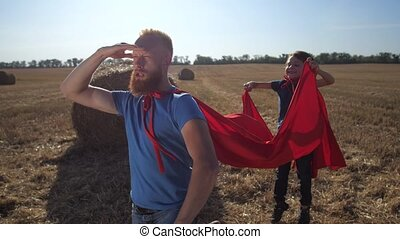 Playful father and son in superhero costumes playing in nature at sundown. Bearded stern male looking into distance, saying motto and showing strong biceps while joyful cute child waving his red cape