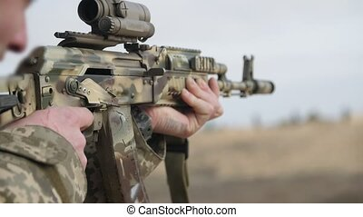Brave man shooting from an automatic rifle with an optical...