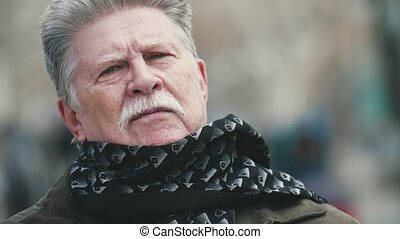 Brave man with a mustache in jacket twisting scarf in autumn...