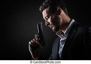 Brave man with handgun - Brave cool man holding a gun on...