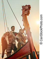 Brave north warrior with his beloved are standing on the bow of a ship and looking at the sea.