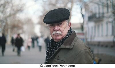Brave old man with a white mustache walking along a street...