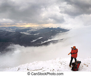 brave photographer takes pictures in the snowy mountains