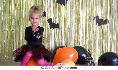 Brave preschooler girl sit on pumpkin and stroke caress big spider with hand. Halloween party decorated room at home. Happy child waiting for evening. Camera motion shot with gimbal.