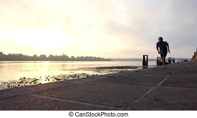 Brave Sportsman Runs on The Riverbank With Concrete Slabs at Sunset in Slo-Mo