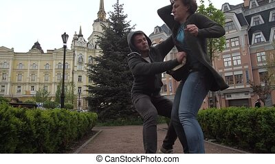 Low angle view of confident female using Krav Maga martial arts to prevent theft attempt during walk in city park. Fearless woman applying self defense beating groin and knocking attaker