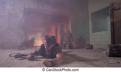Injured military man crawling on his belly on durty floor of smoky ruined building trying to leave place of shelling. Strong-willed wounded army male saving his life during shootout
