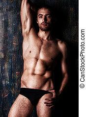 brawny man - Sexual muscular nude man posing over dark...