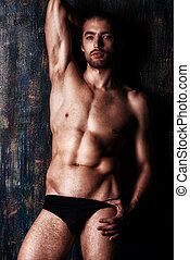 brawny man - Sexual muscular nude man posing over dark...