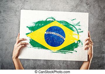 Brazil flag. Man holding banner with Brazilian Flag. ...