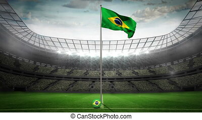 Brazil national flag waving on flagpole in football stadium...