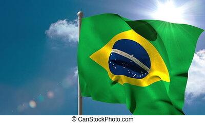 Brazil national flag waving on flagpole on blue sky background