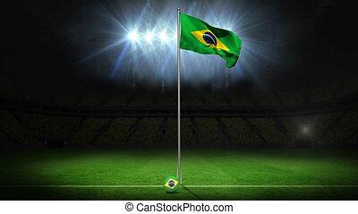 Brazil national flag waving on flagpole on football pitch...