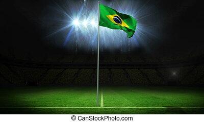 Brazil national flag waving on flagpole against football...