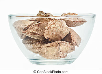 Brazil nuts in a glass bowl isolated on white