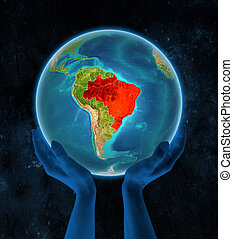 Brazil on Earth in hands in space
