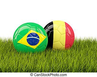 Brazil vs Belgium. Soccer concept. Footballs with flags on green grass