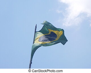 This picture shows a Brazilian flag moving with the wind.