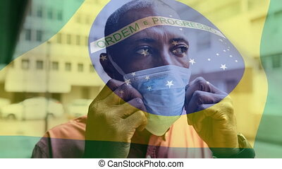 Animation of Brazilian flag waving over mixed race man putting a face mask on. Covid-19 coronavirus national health safety concept digital composite