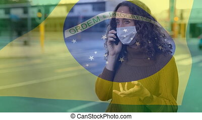 Animation of Brazilian flag waving over mixed race woman wearing a face mask, talking on the phone. Covid-19 coronavirus national health safety concept digital composite