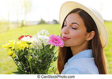 Brazilian pretty beautiful girl smells flowers outdoor
